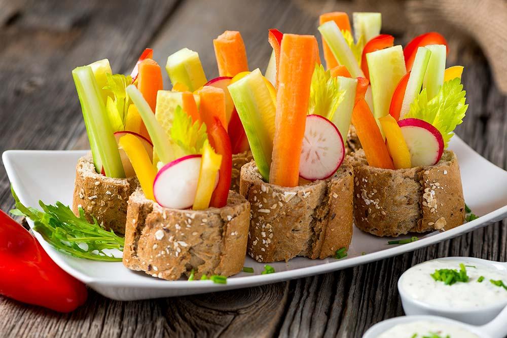 Fingerfood zu Silvester. Etwas dickere Baguettescheiben leicht eindrücken und mit Gemüsestangen, Blättchen und Scheibchen füllen. Dipps in kleinen Portionsschalen dazu reichen. Alle lieben es!